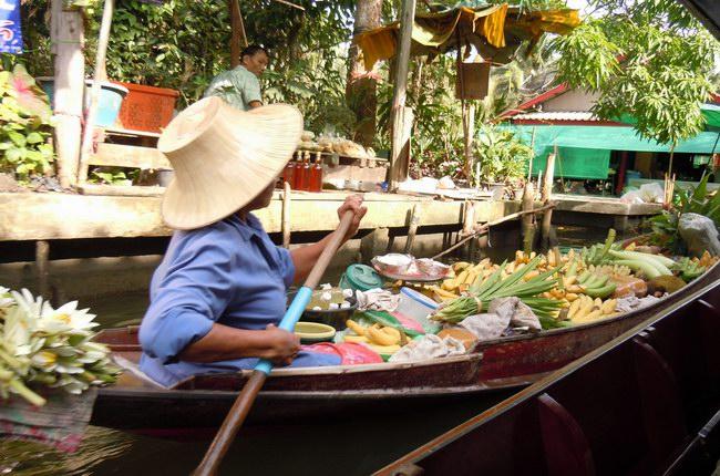 أحد البائعين يأخذ بضائعه في قارب عائم