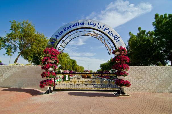 في المدخل قوس من الحديد يحمل اسم الحديقة وتحيطه سلات الزهور
