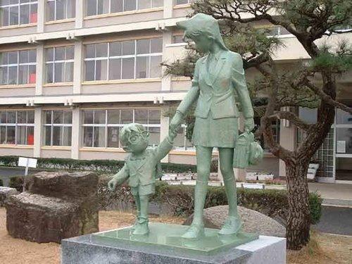 """تمثال لـ """"ران"""" ممسكة بكف المتحري الصغير """"كونان"""" في المدرسة القديمة للرسام """"غوشي أيوما""""."""