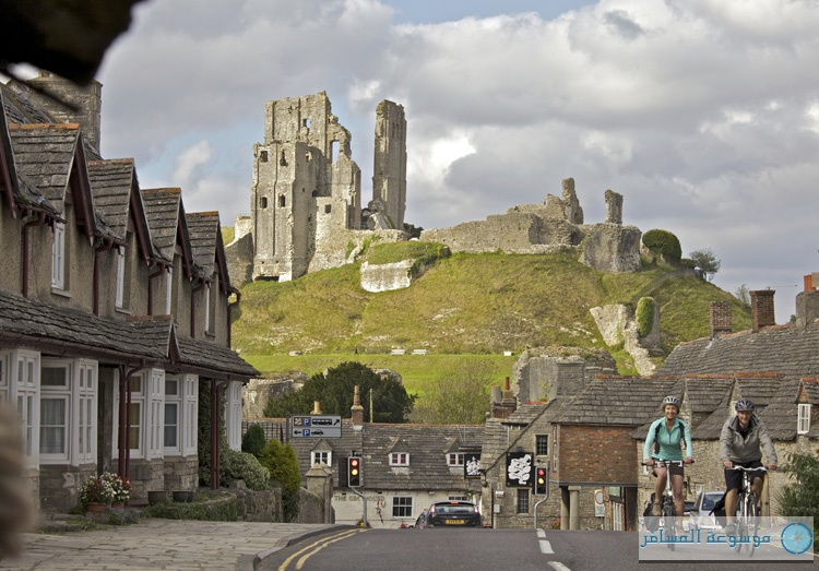 Two cyclists cycling down the road with Corfe Castle in the background